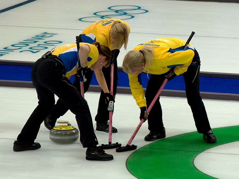 The skip of Team Sweden joins the front end in sweeping a stone into the house at the 2010 Winter Olympics in Vancouver